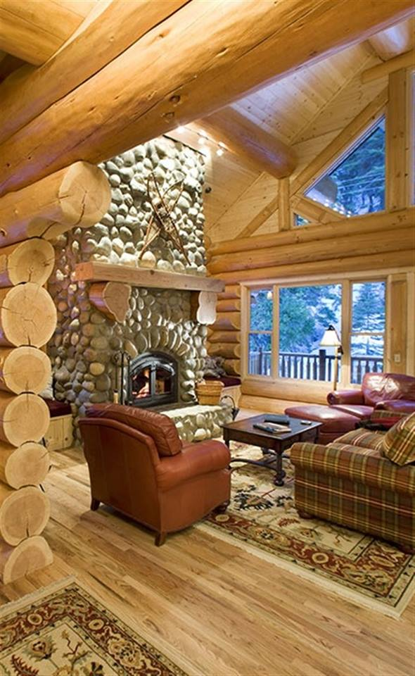 stone fireplace in open space log house living room