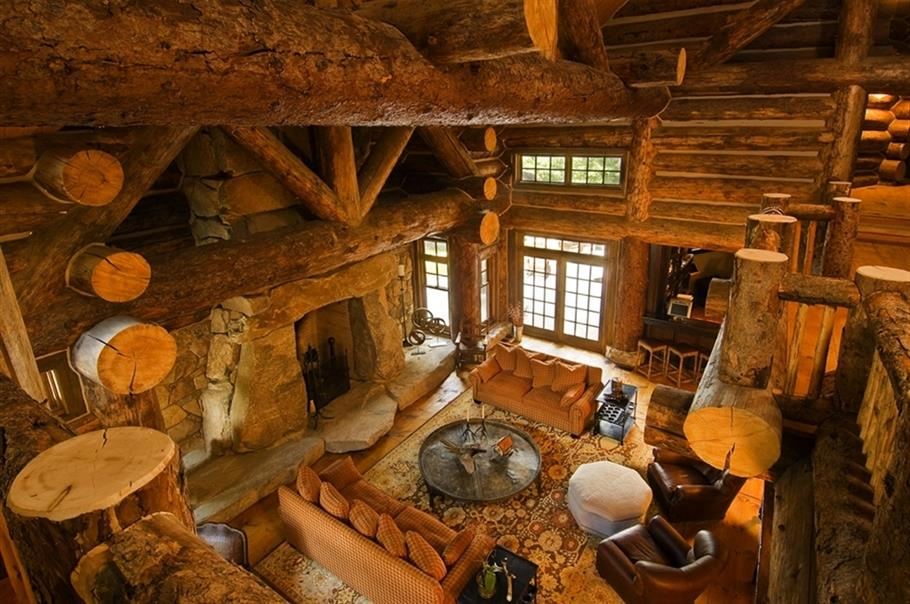 wood interior with big log truss design, living room with fireplace