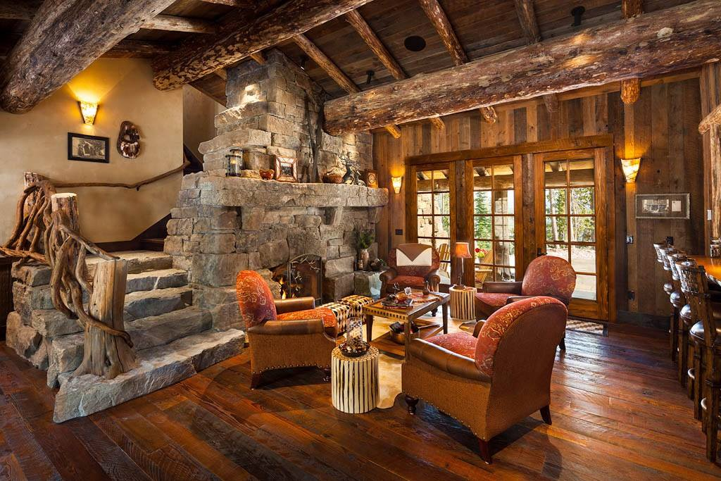 wood log house truss and stone fireplace and staircase