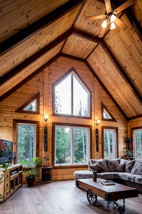 log house interior with large windows and wood walls and ceiling, rustic wheel coffee table