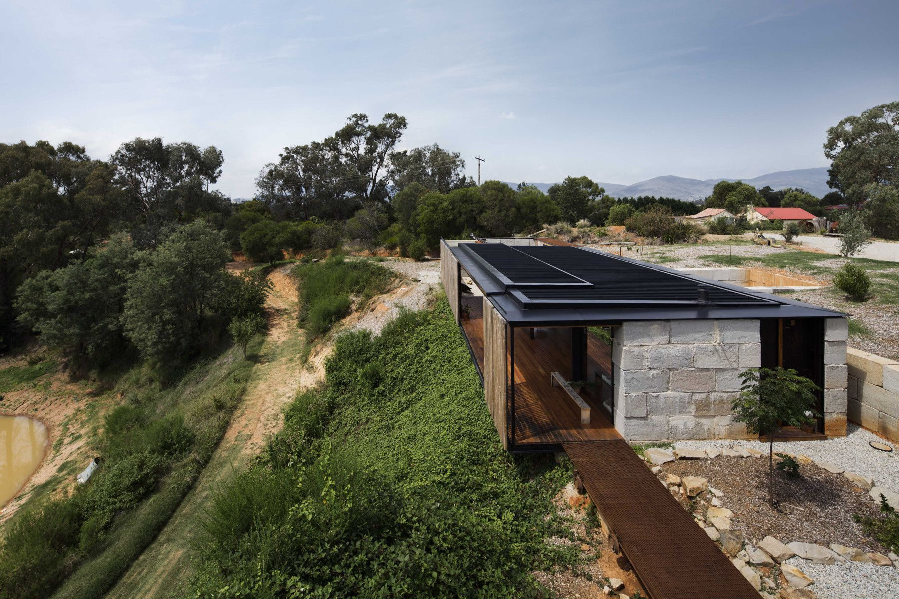The Sawmill House uses large reclaimed one tonne blocks of reclaimed concrete which anchor it into the landscape and a ...