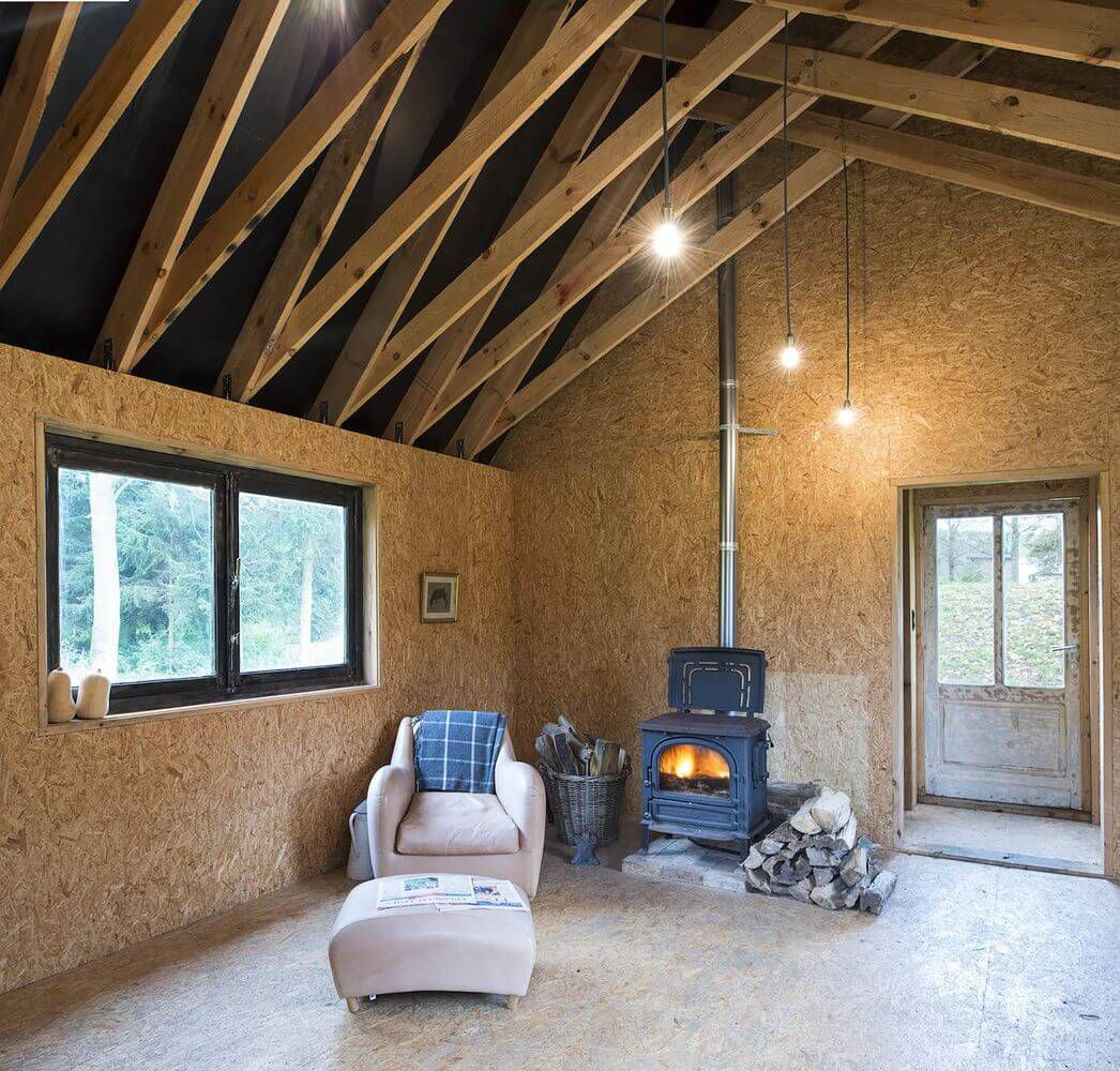 lake cabin interior wood burning stove and osb cladding