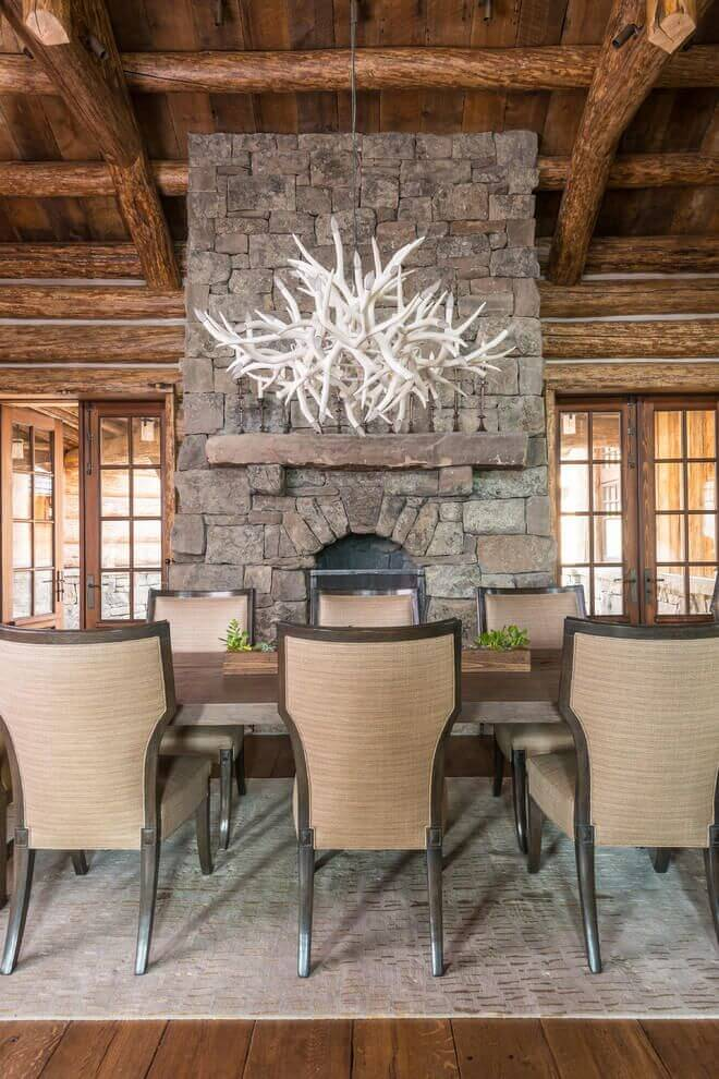 rustic mountain log house luxury dining room with stone fireplace