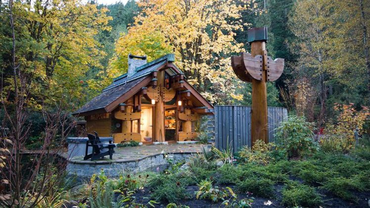 Small cottage designed by Henry Yorke Mann is low structure, supported by totems on all sides and in the middle. ...