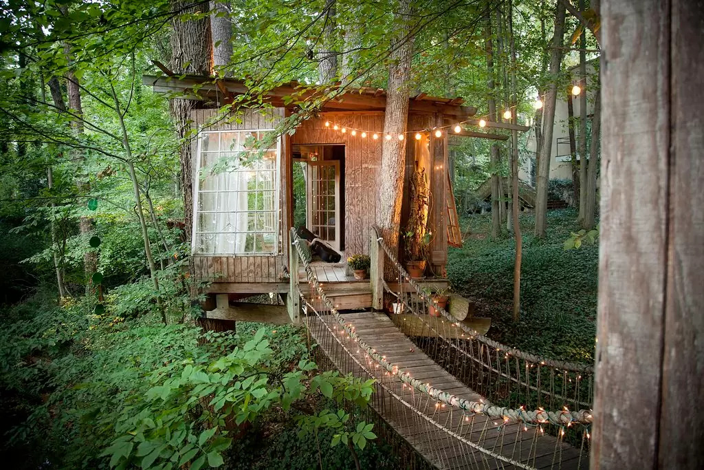 Secluded intown treehouse is made up of three separate areas connected by rope bridges: a living room, a deck with ...