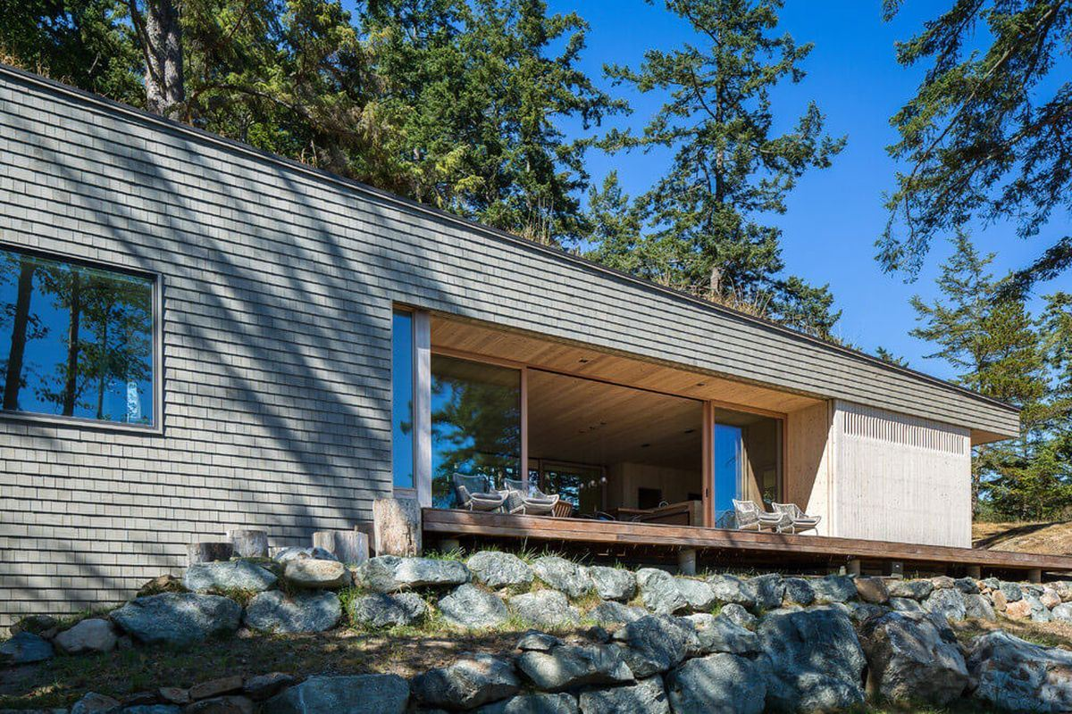 modern wooden retreat house in the woodz and the view to the ocean