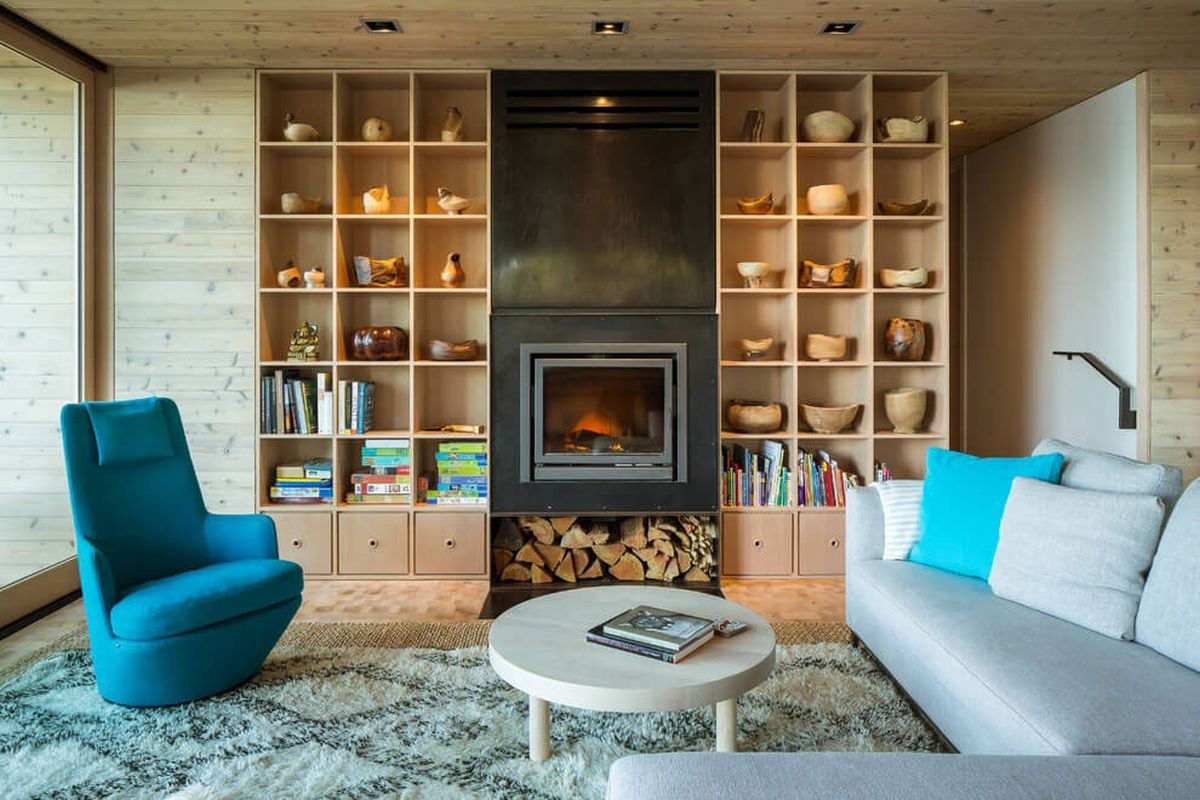 living room with a fireplace and wooden shelves covering the wall