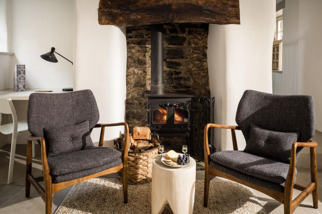 bright cosy fireplace and wooden designed chairs