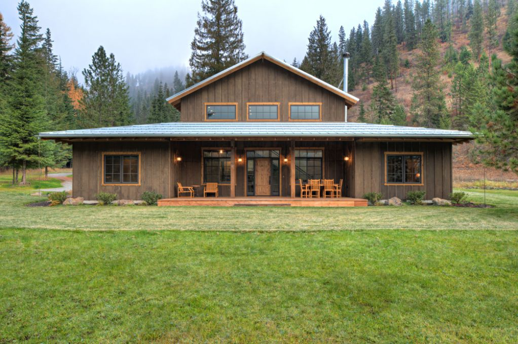 Wooden ranch retreat house / farmhouse with vertical wooden cladding and large porch deck