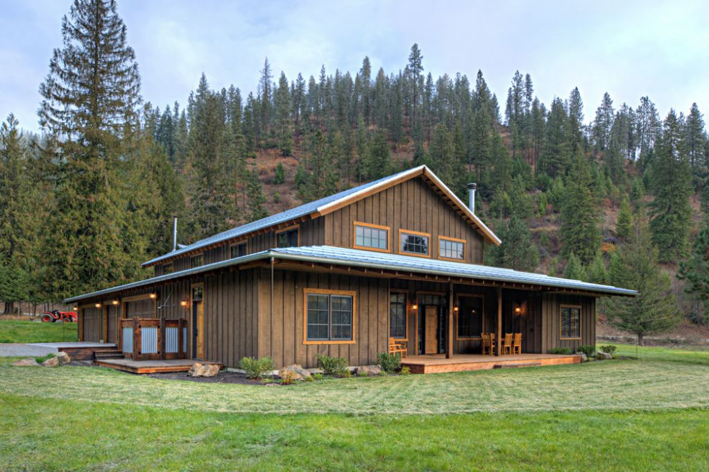 Wooden ranch retreat house / farmhouse with vertical wooden cladding and a large front porch deck