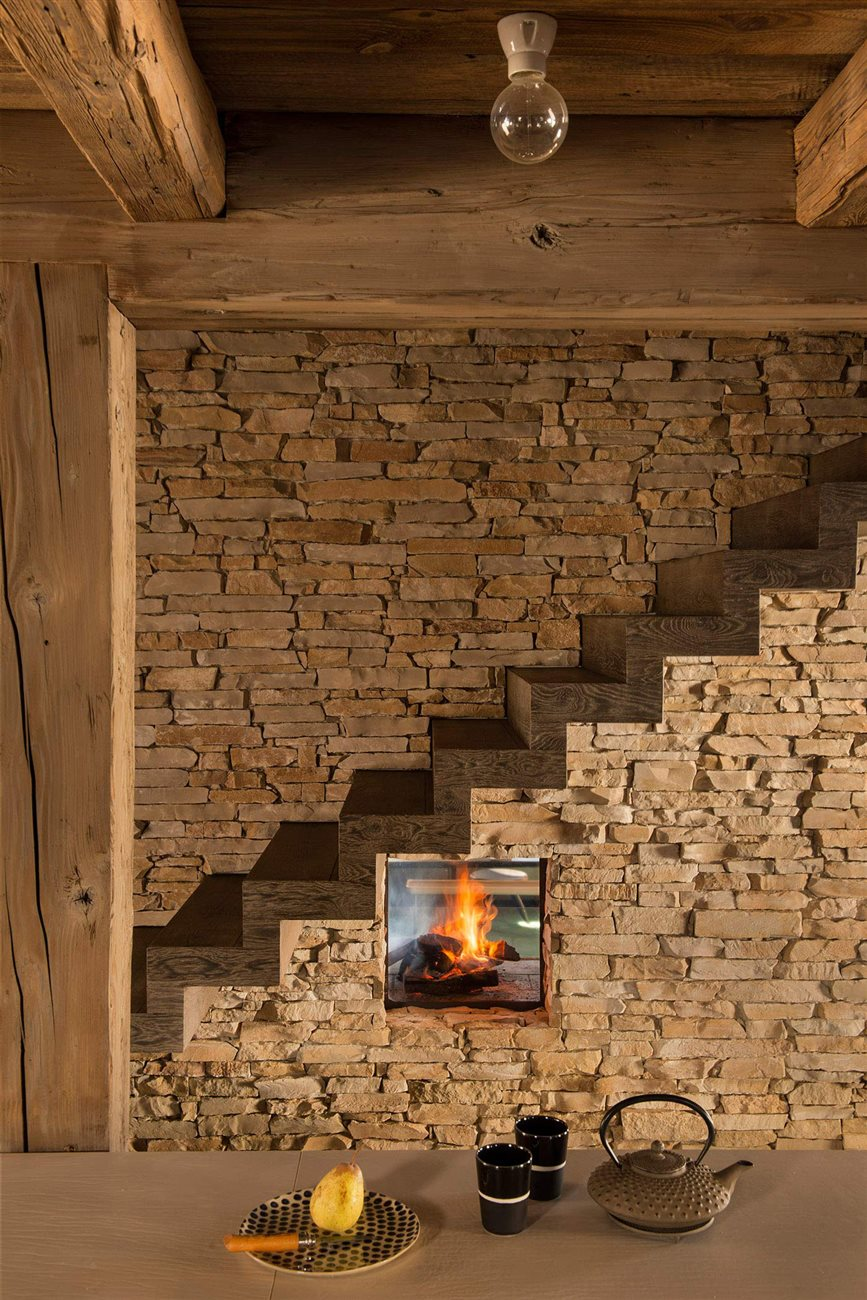 stone wall cladding and wooden pillar and truss on the floating staircase