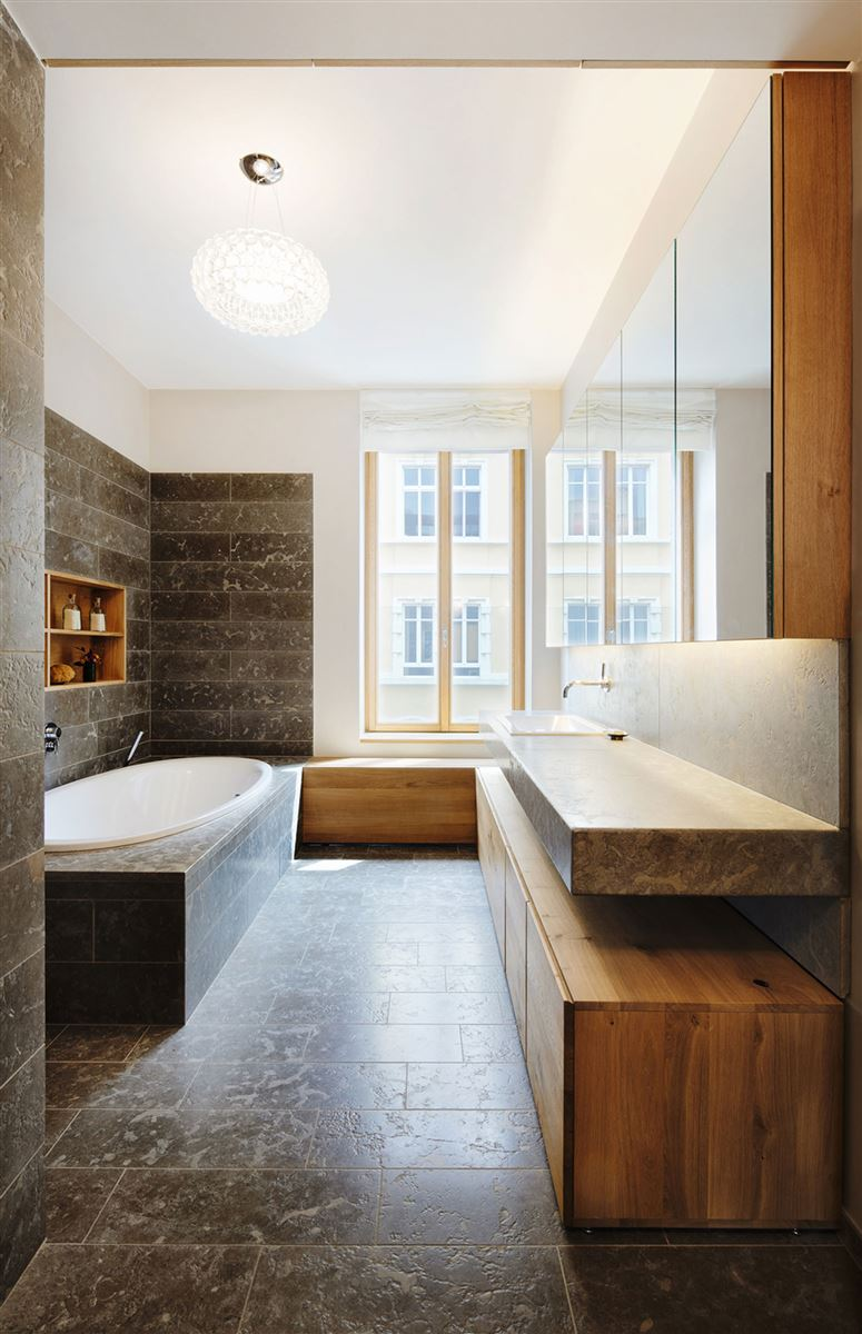 wooden drawers in bathroom with marble tiles and custom made sink
