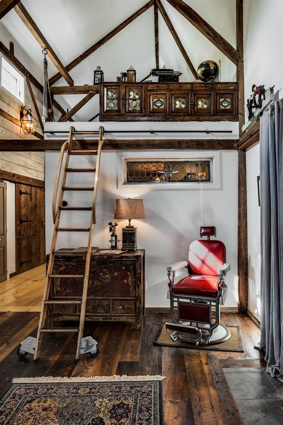 wood rustic interior with ladder and old barber chair in renovated barn