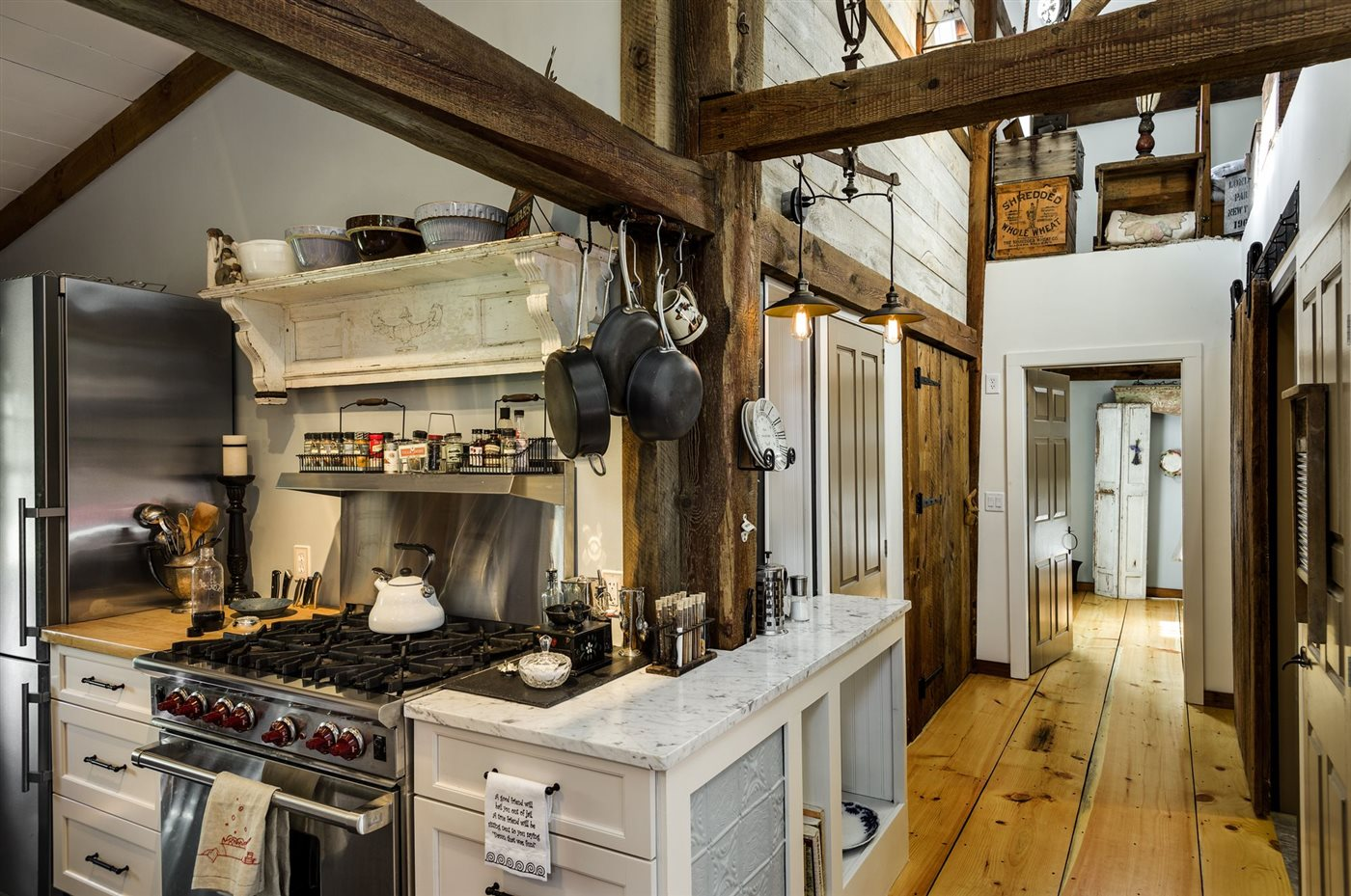 kitchen with marble countertop and wooden truss and columns in renovated barn