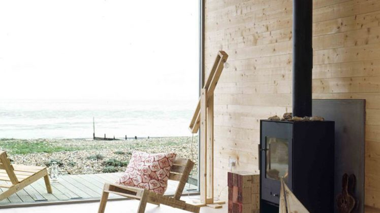 Beach house is built on galvanised steel stilts to prevent flooding. The outside of the chalet is clad with cedar ...