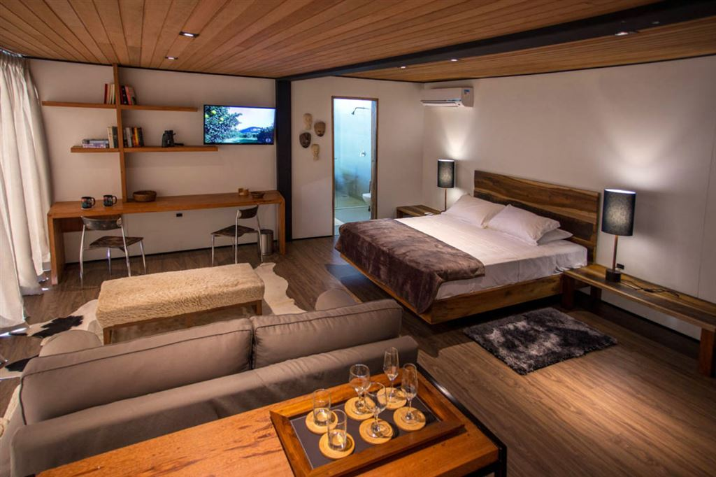 wood interior, bedroom, wooden ceiling and floor, wood table and bed