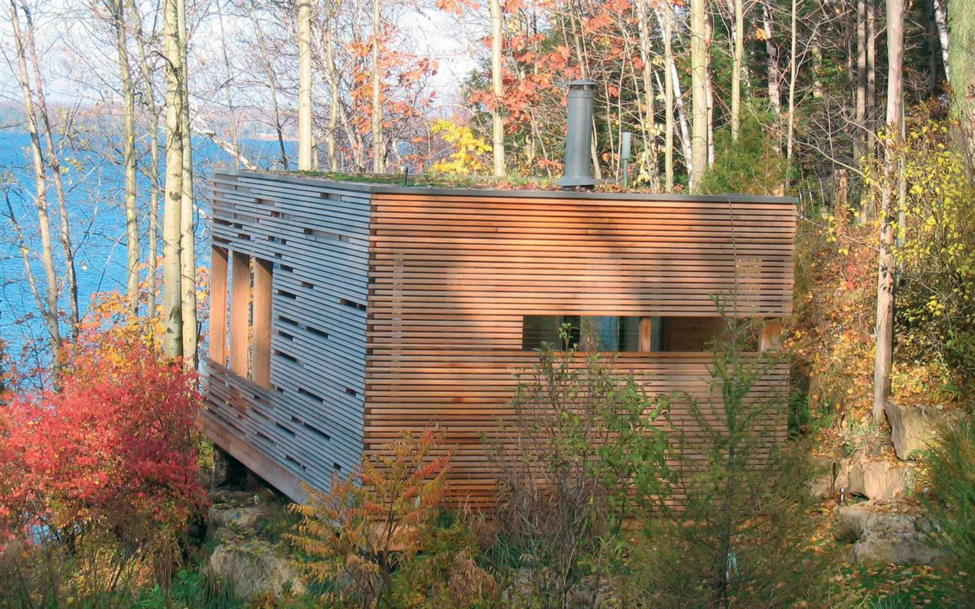 The fully insulated glass cabin is encased on three sides by cedar slats. A green roof is planted with sedums ...